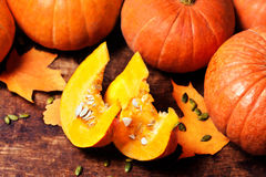 Autumn Pumpkin with pieces over wooden table with copy space / P Royalty Free Stock Images