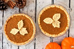 Autumn pumpkin pies with leaf pastry toppings against rustic wood Stock Photos
