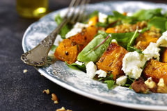 Autumn pumpkin salad with feta,arugula,chard and walnut. Autumn pumpkin salad with feta,arugula,chard and walnut on a vintage plate over dark slate,stone or stock images