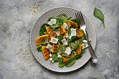 Autumn pumpkin salad with spinach, feta cheese and walnuts.Top royalty free stock photos