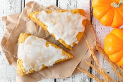 Autumn pumpkin scones with frosting, overhead view on rustic wood Royalty Free Stock Photos