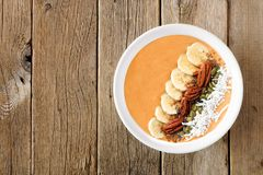 Autumn pumpkin smoothie bowl over a rustic wood background. Autumn pumpkin smoothie bowl with bananas, seeds, nuts, and coconut over a rustic wood background Stock Photo