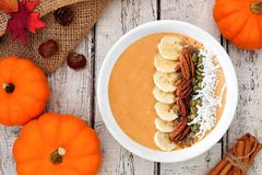 Autumn pumpkin smoothie bowl, scene on white wood Royalty Free Stock Image