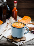 Autumn pumpkin soup in a blue mug, rustic background. Healthy food Stock Images