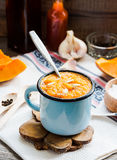 Autumn pumpkin soup in a blue mug, rustic background,selective f. Autumn pumpkin soup in a blue mug, rustic background,healthy food,selective focus Royalty Free Stock Images