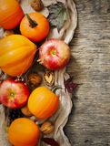 Autumn pumpkins and apples with fall leaves on wooden background Royalty Free Stock Photo