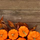 Autumn pumpkins and leaves border on rustic wood background Stock Photo