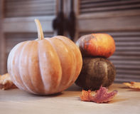 Autumn pumpkins with leaves on wooden table Stock Photography