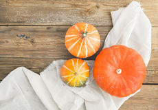 Autumn pumpkins on a piece of linen fabric over a wooden board Royalty Free Stock Image