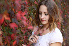 Autumn queen. Young redhead woman next to the autumn colorful leaves royalty free stock photography
