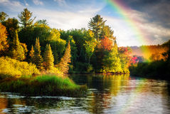 Autumn Rainbow. A scenic lake or river during a light rain displaying a rainbow in the mist on an autumn day close to sunrise or sunset stock image