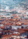Autumn, rainy city through a window with raindrops. Stock Image