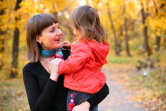 Autumn is a real fun!. Mother and daughter smiling walking together in the park Royalty Free Stock Photography