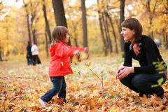 Autumn is a real fun!. Mother and daughter smiling playing together in the park Stock Images