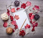 Autumn red leaves on a notebook with a pencil, rattan balls, berries Viburnum concept decorations wooden rustic background top Stock Photography