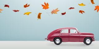 Minimalistic autumn car. Autumn red toy car with fallen leaves against minimalistic blue background Royalty Free Stock Image