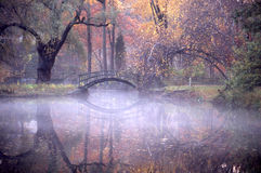 Autumn Reflection. In a pond with a bridge with fog Stock Image
