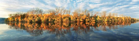 Autumn reflection. Panorama with autumn trees and clouds Stock Photo