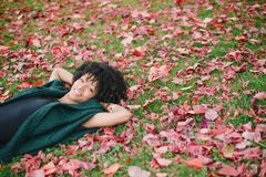 Autumn relax and happiness in the park. Young black happy woman relaxing in autumn outdoor at the park. Happiness and relax concept Royalty Free Stock Photo