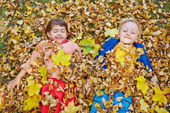 Autumn relax. Happy friends with closed eyes lying in dry autumn leaves Stock Photos