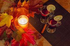 Autumn relaxation concept. Two glasses of mulled wine and a burning candle surrounded by maple leaves on a wooden table royalty free stock photo
