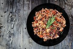 Autumn rice pilaf with apples and cranberries. In a black plate against an old wood background Royalty Free Stock Photos