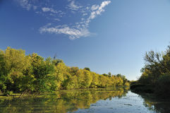 Autumn by river. Early autumn sunny day by river with colorful trees reflection on water Stock Photography