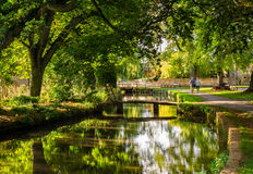 Autumn river in the Cotswolds, England. Couple walk in the village of Lower Slaughter, Cotswolds, England, in early autumn Stock Photography