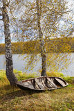 Autumn river with an old boat Stock Photos