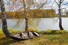 Autumn river with an old wooden boat Stock Photography