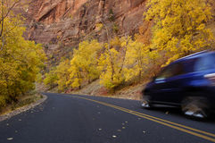 Autumn road 1. Autumn road in Zion National Park, Utah. Yellow foliage, red rocks and a motion-blurred blue car zooming by Stock Photos