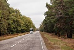 Autumn road allowing to move loads by trucks. Direct line lonely truck moving cargo stock image