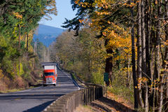 Autumn road with beautiful scenery and red semi truck Stock Image