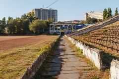 Autumn road on the destroyed stadium against the blue sky Stock Photos