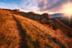 Autumn road in mountains on background of sunset sky Royalty Free Stock Photography