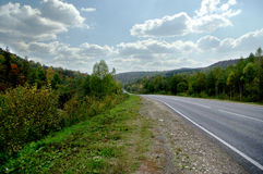 Autumn road in the mountains. Colorful forest Royalty Free Stock Photography