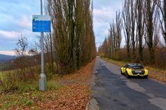 Yellow sport car on old autumn road. Autumn road in slovakia country royalty free stock photography