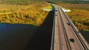 Autumn road view from above. Highway on autumn background. Road river landscape. Car bridge over river and highway road. Aerial view cars driving over highway stock footage