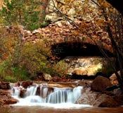 Autumn Rock Bridge. An old sturdy rock bridge with a slow flowing stream cutting through the Autumn foliage stock photography