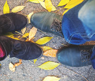 Autumn romance. Legs of man and woman on fallen leaves Stock Photography