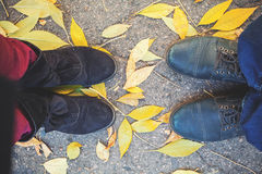 Autumn romance. Legs of man and woman on fallen leaves Royalty Free Stock Photo