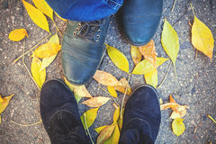Autumn romance. Legs of man and woman on fallen leaves Royalty Free Stock Photography