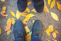 Autumn romance. Legs of man and woman on fallen leaves Stock Photo