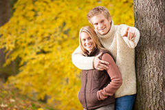 Autumn romantic couple smiling together in park. Autumn romentic couple happy together hugging in park tree pointing royalty free stock photography