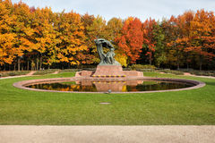 Autumn in Royal Lazienki Gardens in Warsaw. Fryderyk Chopin monument, designed around 1904 and autumn scenery of the Royal Lazienki Gardens in Warsaw, Poland royalty free stock images