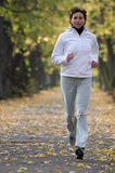 Autumn running. Woman running in autumn park Royalty Free Stock Photography