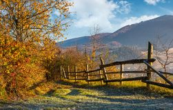 Autumn rural scenery with fence on hillside. Yellow foliage on trees and mountain ridge in a distance under the blue sky Stock Images