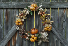 Autumn's Bounty Wreath. Decorative autumn wreath depicting various crops hanging on a rustic wooden fence Royalty Free Stock Photo