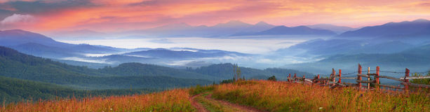 Autumn`s mystery. A beautiful morning panoramic scenery in the Ukrainian Carpathian mountains in the fall, with white fog flowing in between the hills and Stock Photo