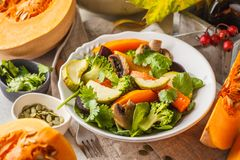 Autumn salad from baked pumpkin, beet, zucchini and carrots. Healthy vegan food concept. Autumn food concept stock photos